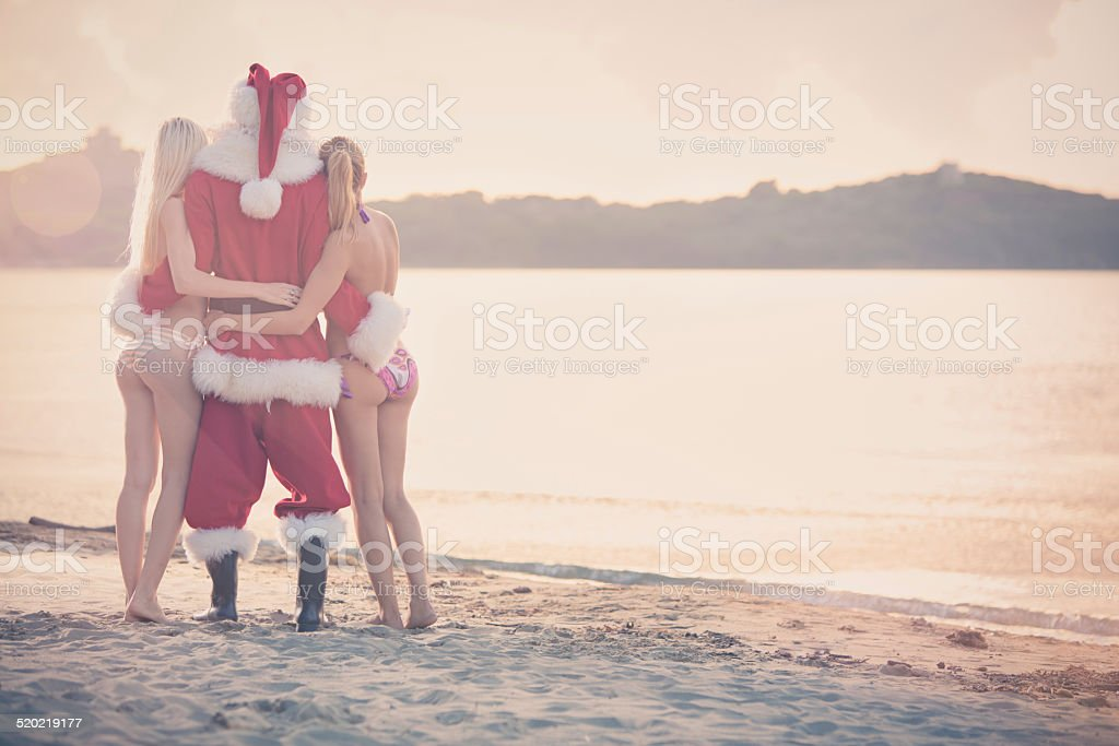 Santa Claus and beautiful girl standing at sunset on shore stock photo