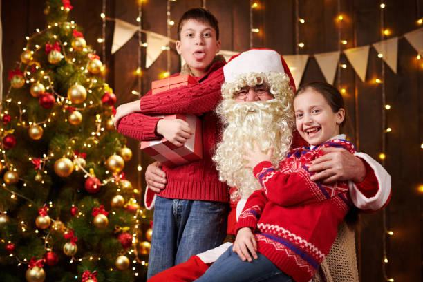 Papá Noel y niño niño y niña posando juntos interior cerca decorado árbol de Navidad con luces, que hablan, sonriendo y aceptando regalos - Feliz Navidad y Felices Fiestas! - foto de stock
