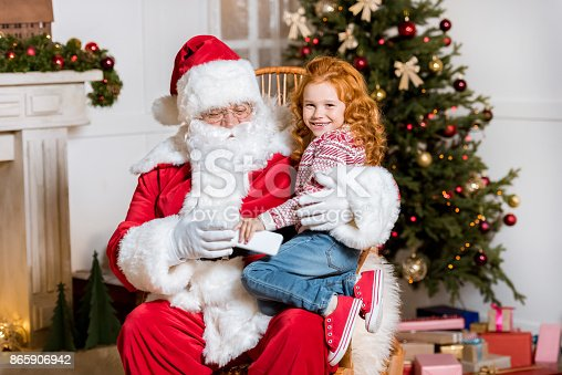 portrait of smiling little girl with present sitting on santa claus knees
