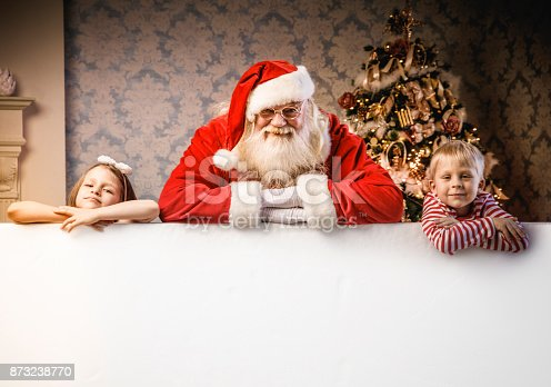 istock Santa Claus and kids pointing on blank banner 873238770