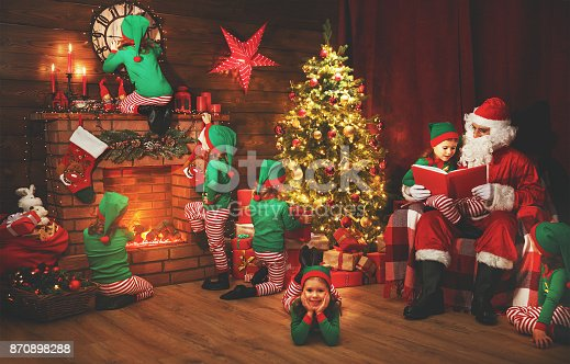 istock Santa Claus and little elves before Christmas in his house 870898288