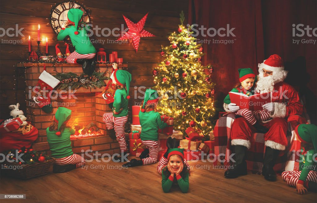 Santa Claus and little elves before Christmas in his house stock photo