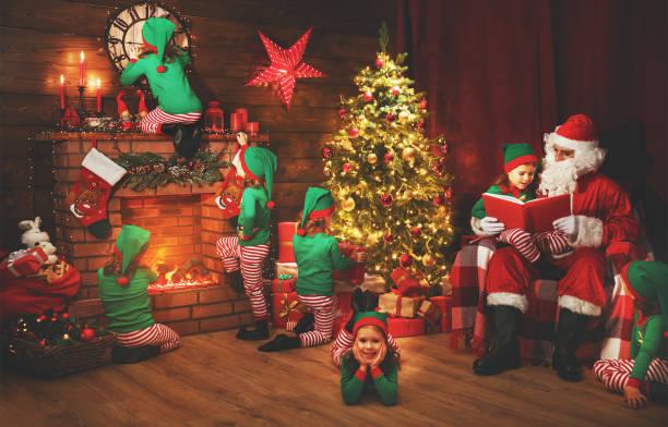 santa claus und kleinen elfen vor weihnachten in seinem haus - nikolaus kostüm stock-fotos und bilder