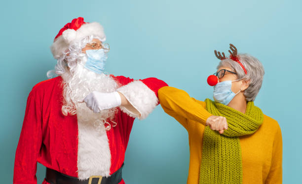 Santa Claus and reindeer in face masks during Covid-2019 stock photo