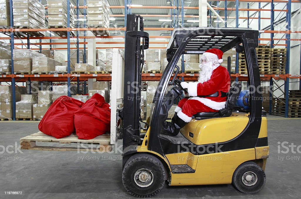 Santa Claus as a forklift operator at work in warehouse stock photo