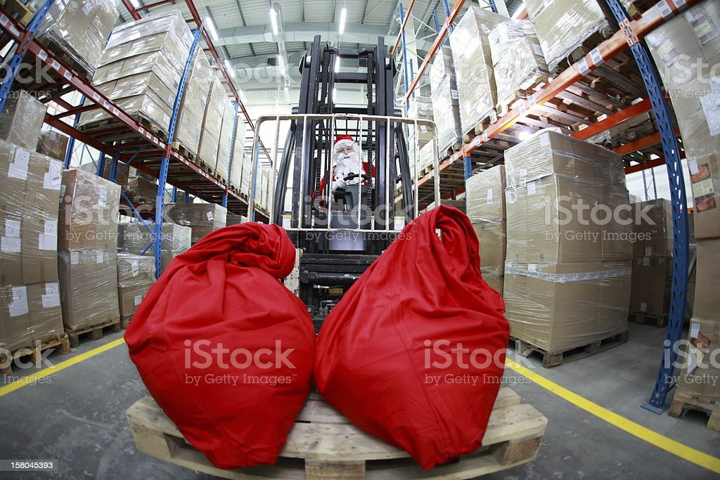 Santa Claus as a forklift operator at work in warehouse royalty-free stock photo