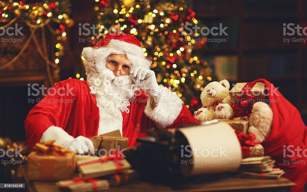 Santa claus at desk with letters gifts near christmas tree stock santa claus at desk with letters gifts near christmas tree royalty free stock photo spiritdancerdesigns Gallery