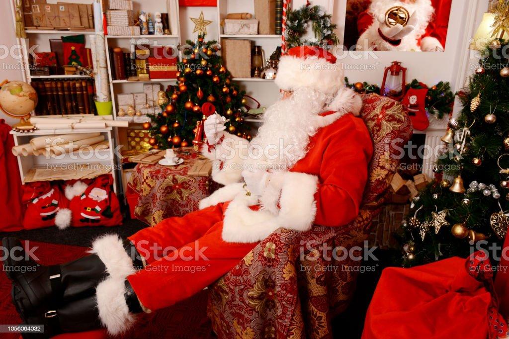 Santa Claus at his home looking at pocket watch - Zbiór zdjęć royalty-free (Biurko)
