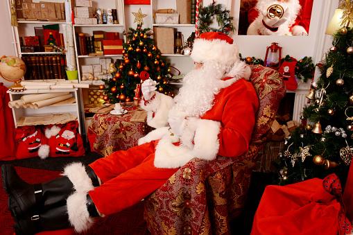Santa Claus At His Home Looking At Pocket Watch - zdjęcia stockowe i więcej obrazów Biurko