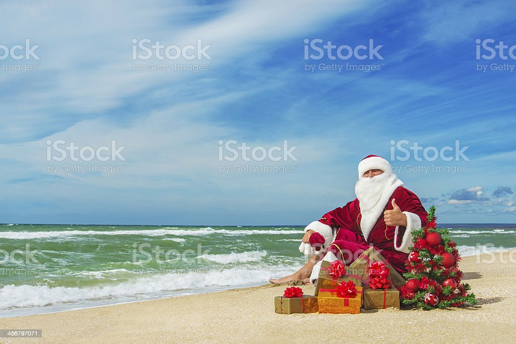Santa Claus at sea beach with gifts and christmas tree stock photo