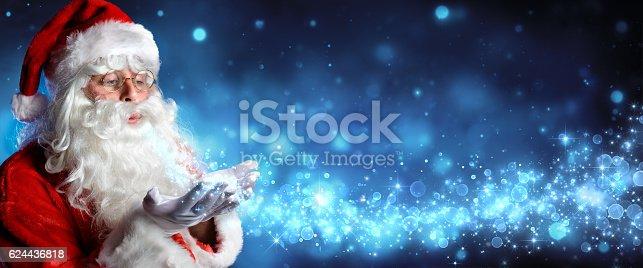 istock Santa Claus Blowing Magic Christmas Stars In Snowy Night 624436818