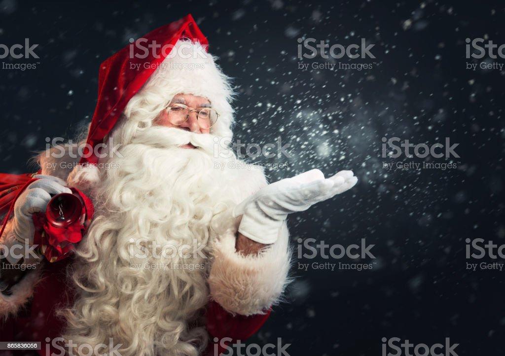Santa Claus blowing magic snow of his hands royalty-free stock photo