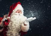 彼の手の魔法の雪を吹くサンタ クロース