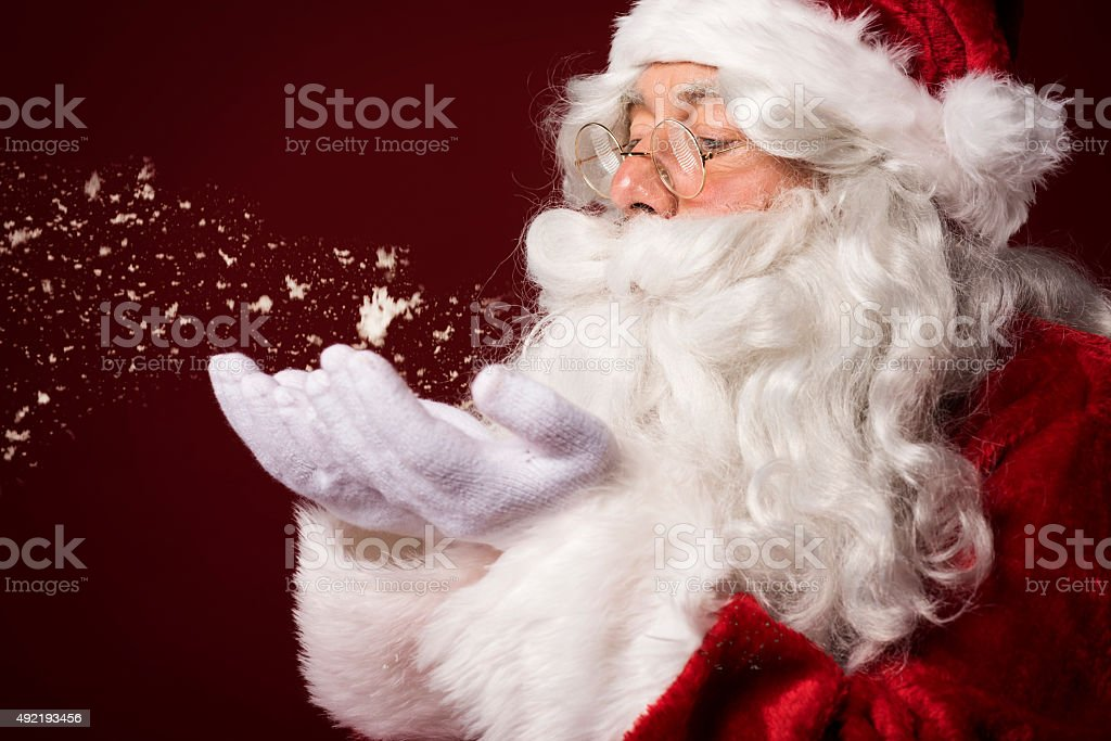 Santa claus blowing some snowflakes stock photo