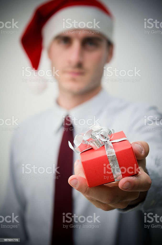 Santa Claus business man holding a present stock photo