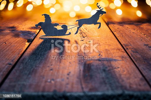 Cute christmas decoration with a light in a jar and some christmas ornaments. Jar is decorated with a bow, wooden christmas tree and a cut paper silhouette of santa claus in a sled and reindeer.