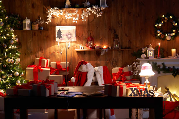 santa claus costume and hat hanging on chair at table with merry christmas decor gifts presents on holiday eve in cozy santa home workshop interior late in night with light on xmas tree and fireplace. - fundo oficina imagens e fotografias de stock