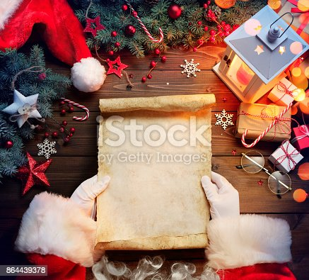 istock Santa Claus Desk Reading Wish List With Ornament And Christmas Gift 864439378