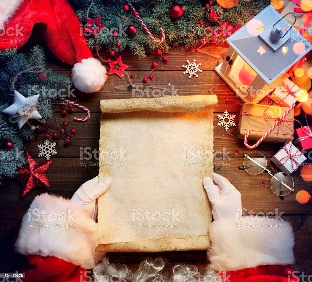Santa Claus Desk Reading Wish List With Ornament And Christmas Gift stock photo