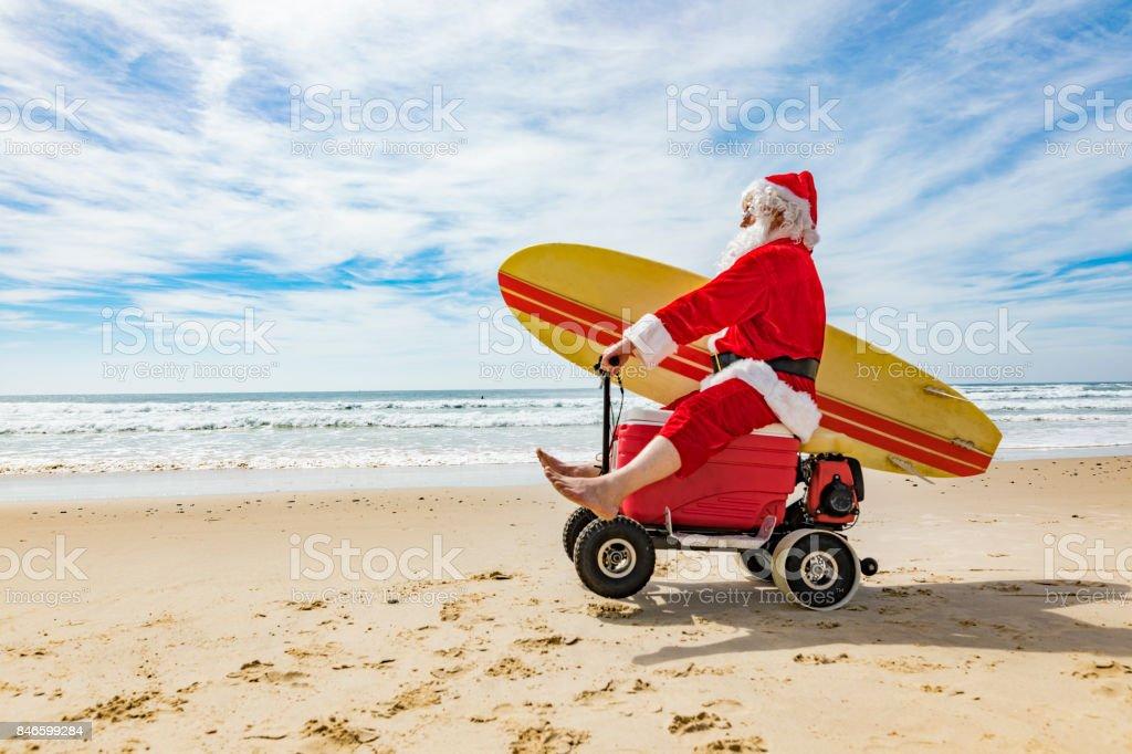 Santa Claus Doing a Wheelie on a Motorised Esky Cooler on the Beach stock photo