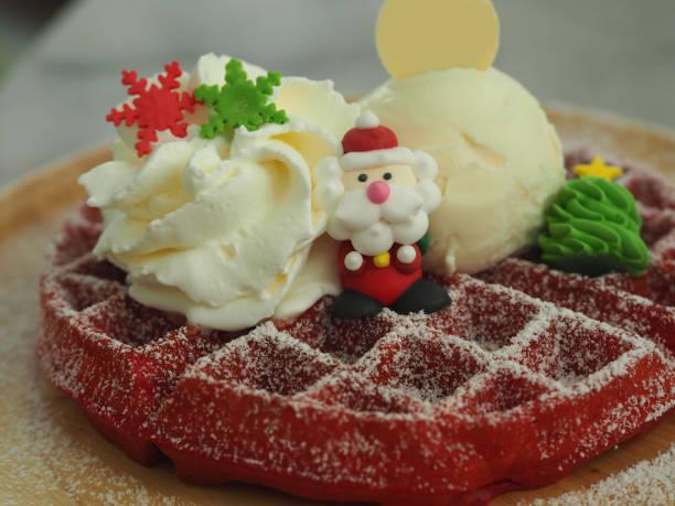 weihnachtsmann puppe auf red velvet waffel, frohe weihnachten - weihnachtsmannhüte aus erdbeeren stock-fotos und bilder
