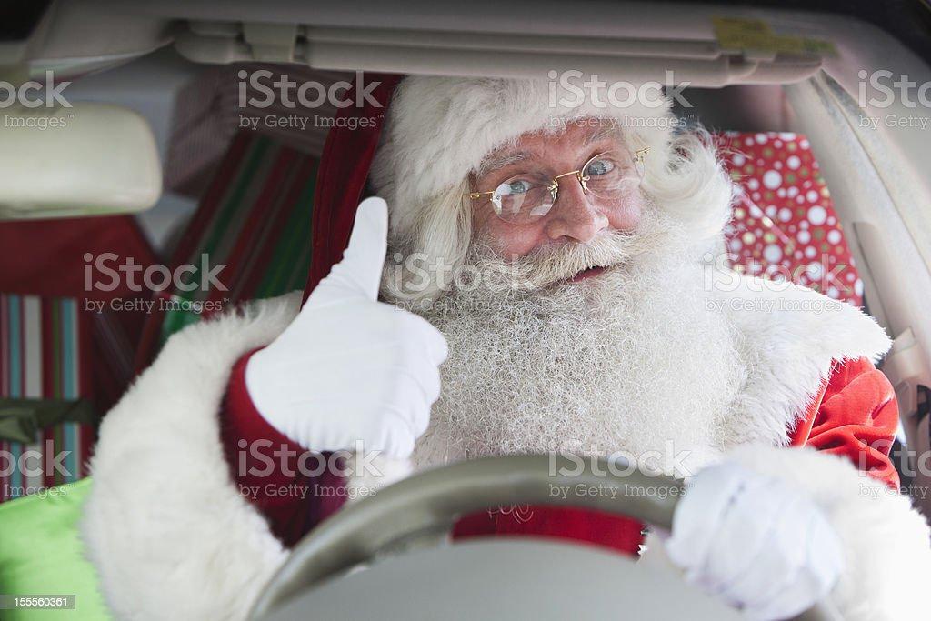 Santa Claus conducir un vehículo con un montón de regalos thumbs up - Foto de stock de 60-64 años libre de derechos
