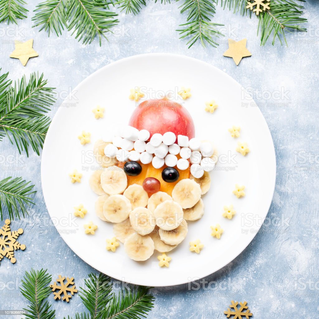 Santa Claus face made of fruits and marshmallow on a plate. Christmas food for children. Top view stock photo