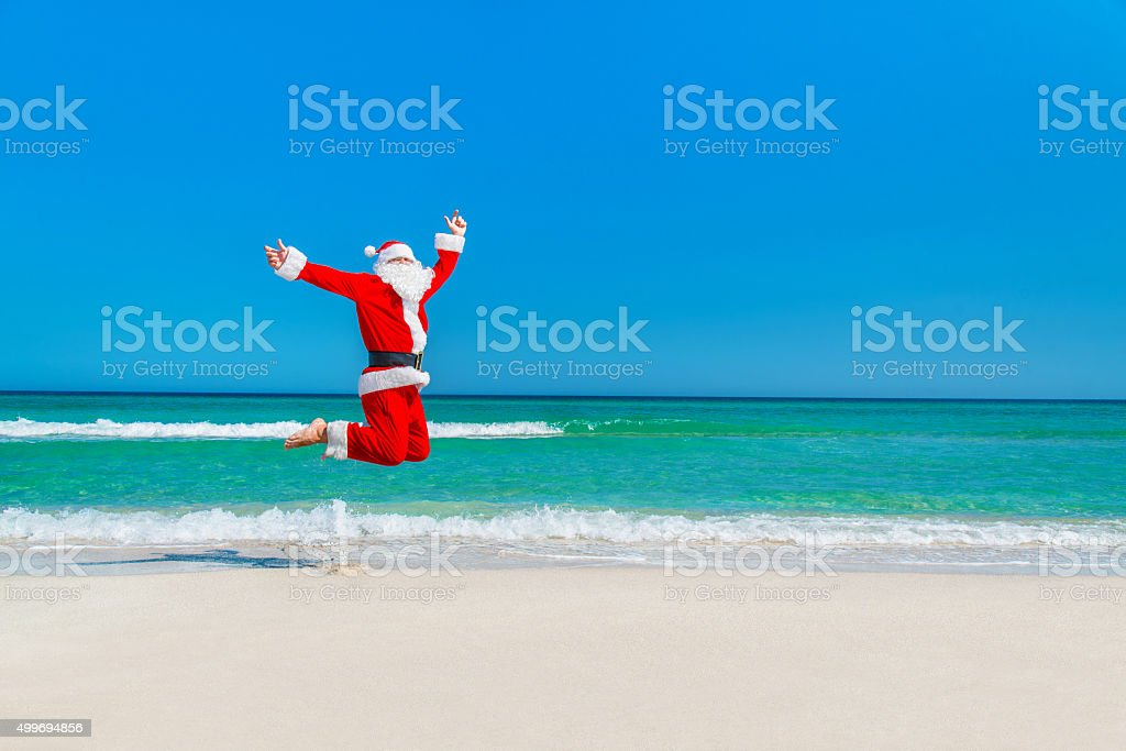 Santa Claus flying against sea beach and sky, Christmas concept stock photo