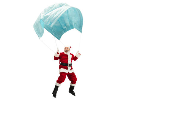 Santa Claus flying on huge face mask like on balloon isolated on white background Santa Claus flying on huge face mask like on balloon isolated on white background. Caucasian male model in traditional costume. New Year, gifts, holidays, winter, COVID, pandemic concept. Copyspace. funny christmas stock pictures, royalty-free photos & images