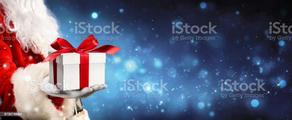 Santa Claus Giving A Giftbox In Magic Night - foto stock