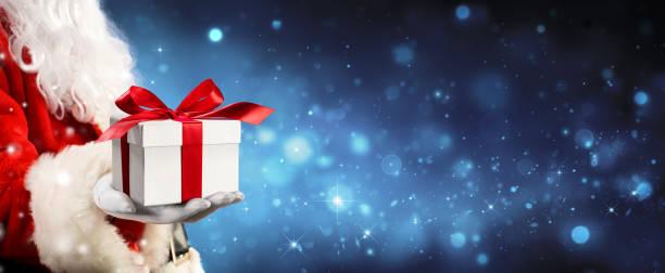 santa claus geben eine geschenkbox in magische nacht - nikolaus kostüm stock-fotos und bilder