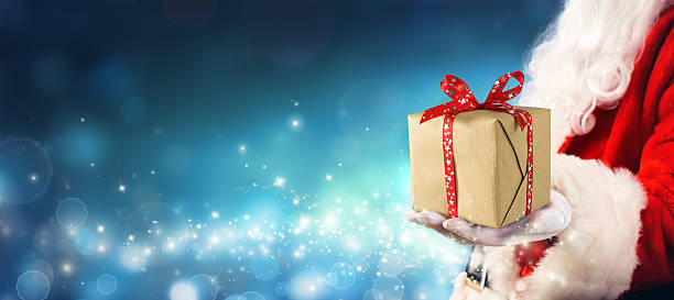 Santa Claus Giving Gift Box In Magic Night stock photo