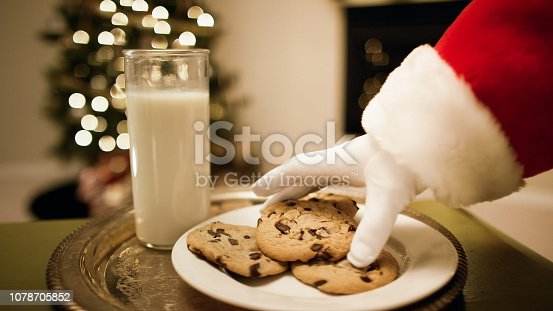 Santa Claus' Gloved Hand Picks Up a Chocolate Chip Cookie from a Tray with a Glass of Milk on It with a Christmas Tree and a Fireplace in the Background on Christmas Eve