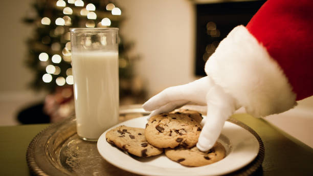 santa claus' gloved hand picks up a chocolate chip cookie from a tray with a glass of milk on it with a christmas tree and a fireplace in the background on christmas eve - bolachas imagens e fotografias de stock