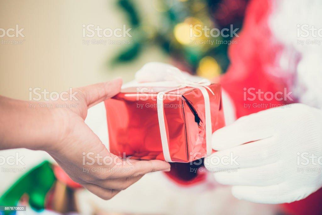 Santa claus gehandschoende handen met luxegeschenketui op kamer