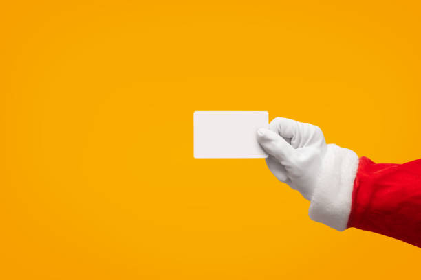 Santa Claus hand holding plastic credit card over isolated background. stock photo