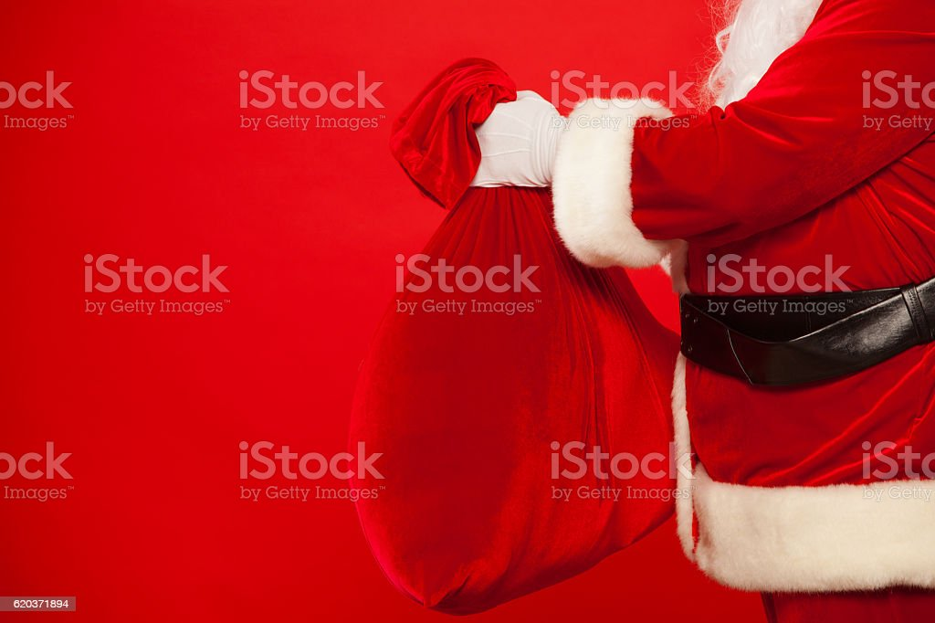 Santa Claus hand holding red sack full of presents over foto de stock royalty-free