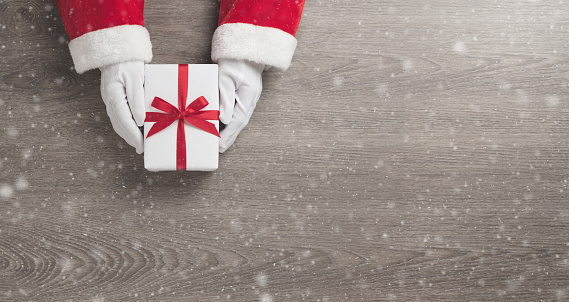 Merry Christmas concept, Top view of Santa claus hands is holding a white gift box with red ribbon and snow on wooden background. Banner, Panoramic view for web. Copy space.