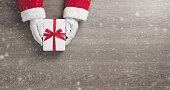 istock Santa claus hands is holding a white gift box with red ribbon 1171480363