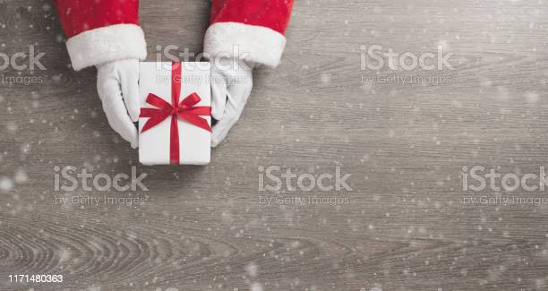 Santa claus hands is holding a white gift box with red ribbon picture id1171480363?b=1&k=6&m=1171480363&s=612x612&h=hevoulvwojpwhdtfkmkuyx2qzv7uzz6afftvojbnirw=