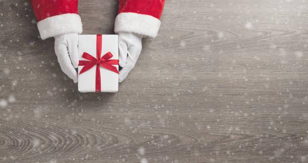 santa claus hände hält eine weiße geschenkbox mit rotem band - santa stock-fotos und bilder