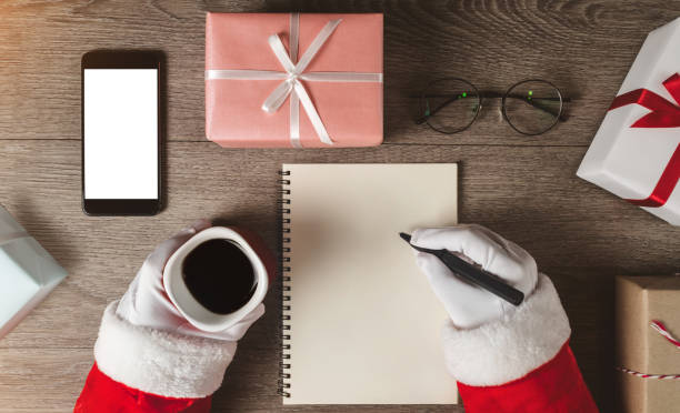 Santa Claus hands is writing something in a blank notebook. stock photo