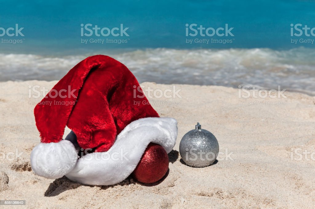 Santa Claus Hat and Christmas decorations at the sandy tropical beach with sea as a background stock photo