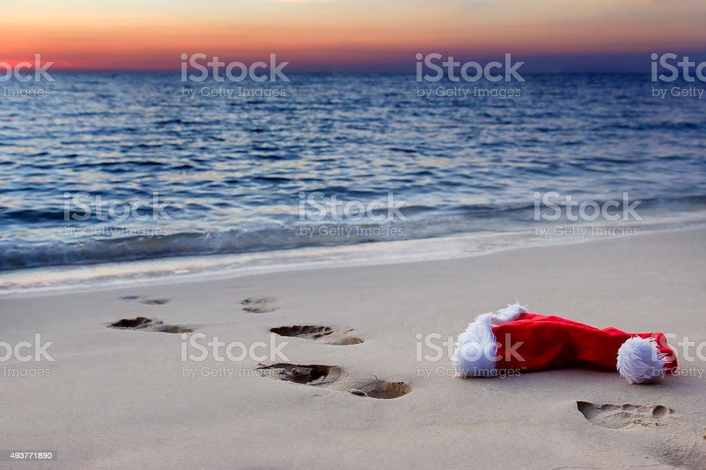 Santa Claus hat on beach at sunset stock photo