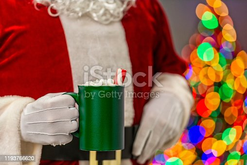 Santa Claus holding a large green mug with steaming hot chocolate that has mini marshmallows and a large candy can stick in it along with bokeh of multi-colored Christmas tree lights in the background.