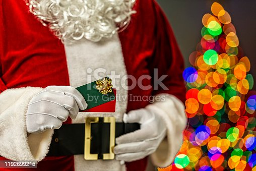 Santa Claus holding a pair of gift cards with a gold bow and in the background the bokeh of multi-colored Christmas tree lights