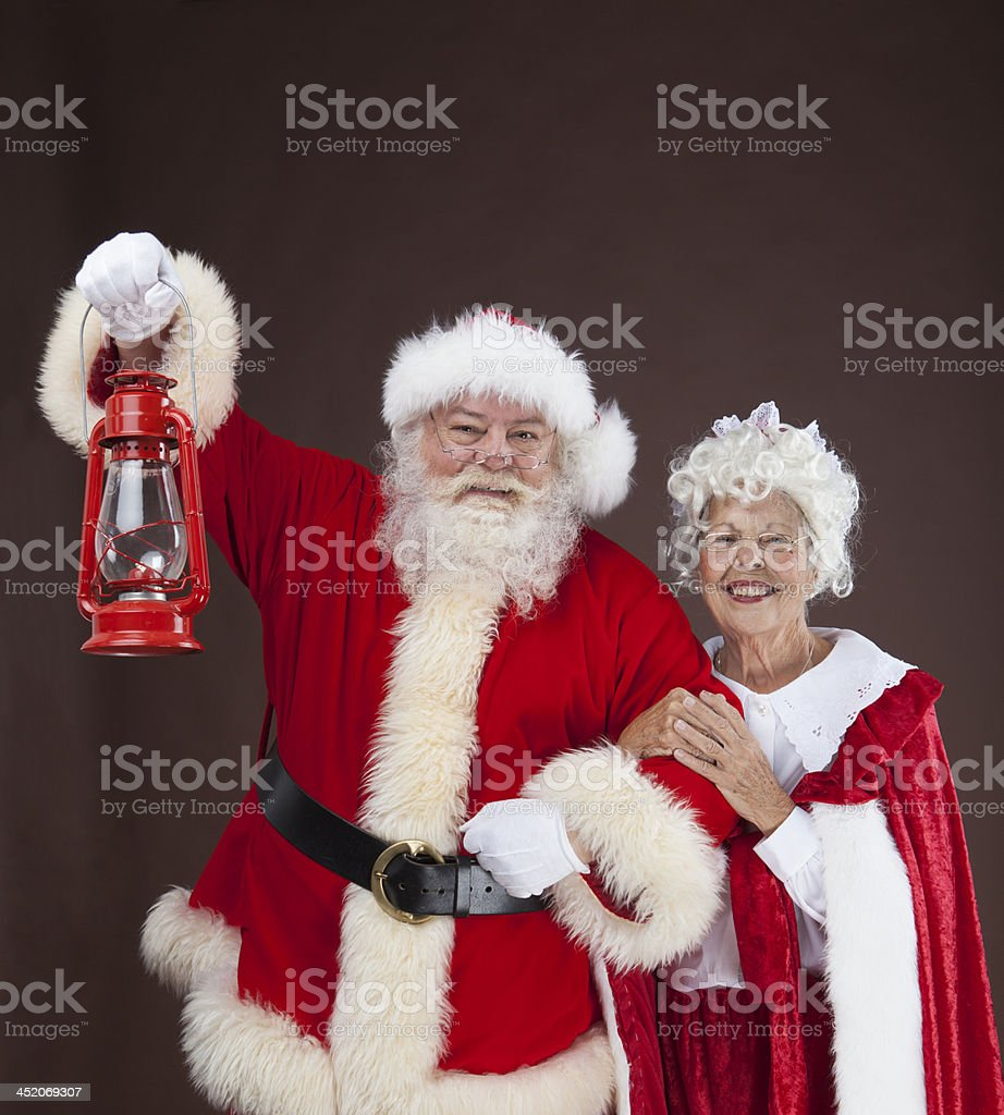 Santa Claus holding an unlit lantern with Mrs Claus stock photo