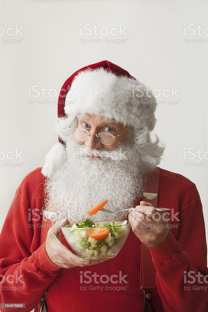 Santa claus holding bowl with salad royalty-free stock photo