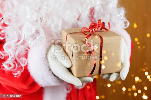 Santa Claus holding gift box against blurred Christmas lights. Happy Christmas.
