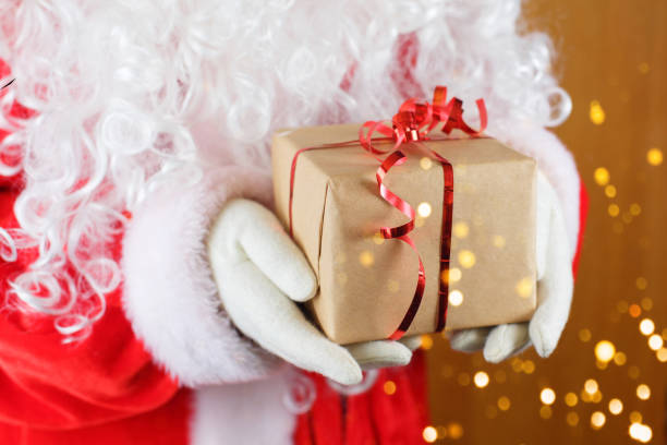 Santa Claus holding gift box against blurred Christmas lights stock photo